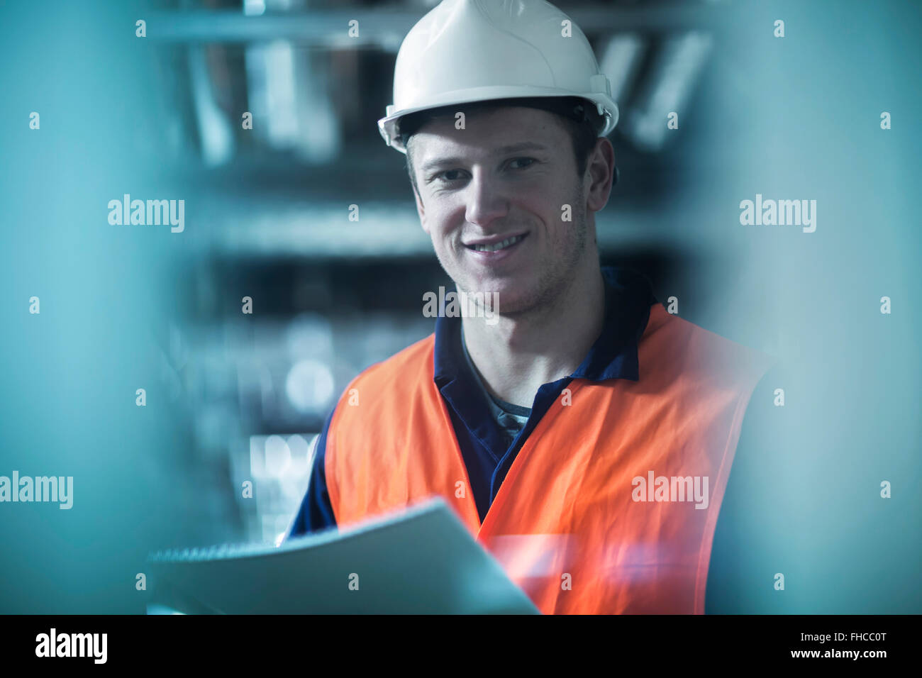 Portrait of smiling young man with safety clothes in technical room - Stock Image