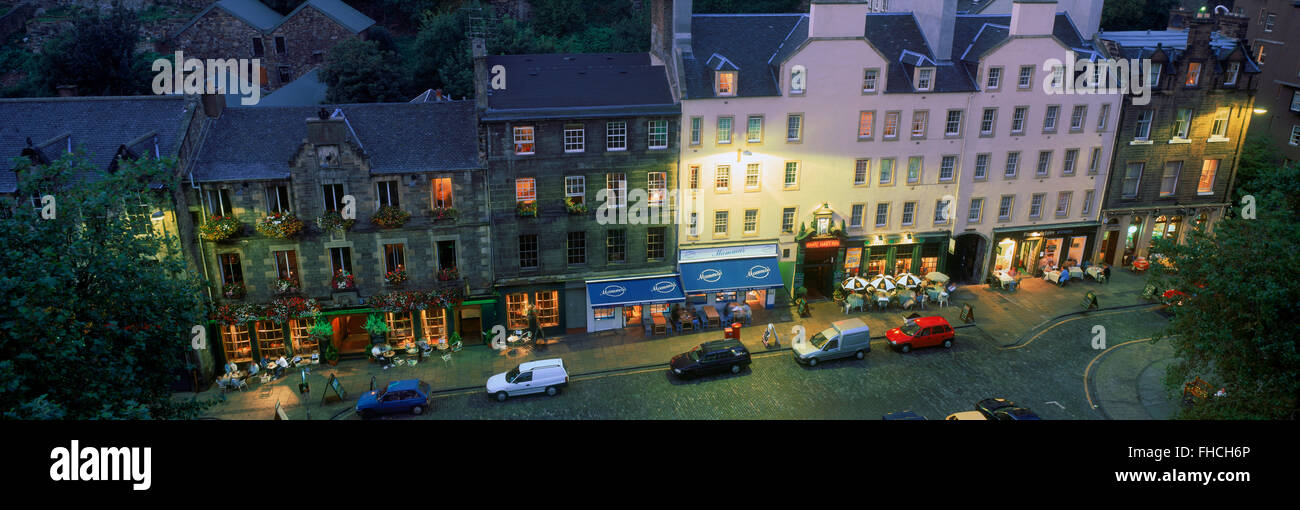Panoramic overview of cars parked at old pubs along Grassmarket in Edinburgh in dusk light in Scotland - Stock Image
