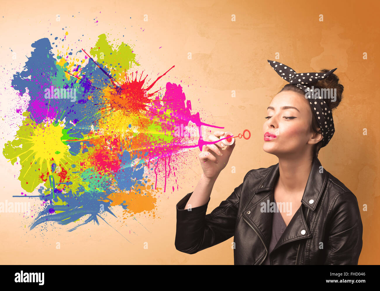Cute girl blowing colorful splash graffiti - Stock Image