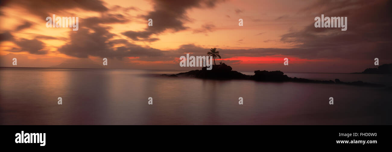 Panoramic photo of couple on rocky point with one palm tree off Mahe Island in Seychelles at sunset - Stock Image