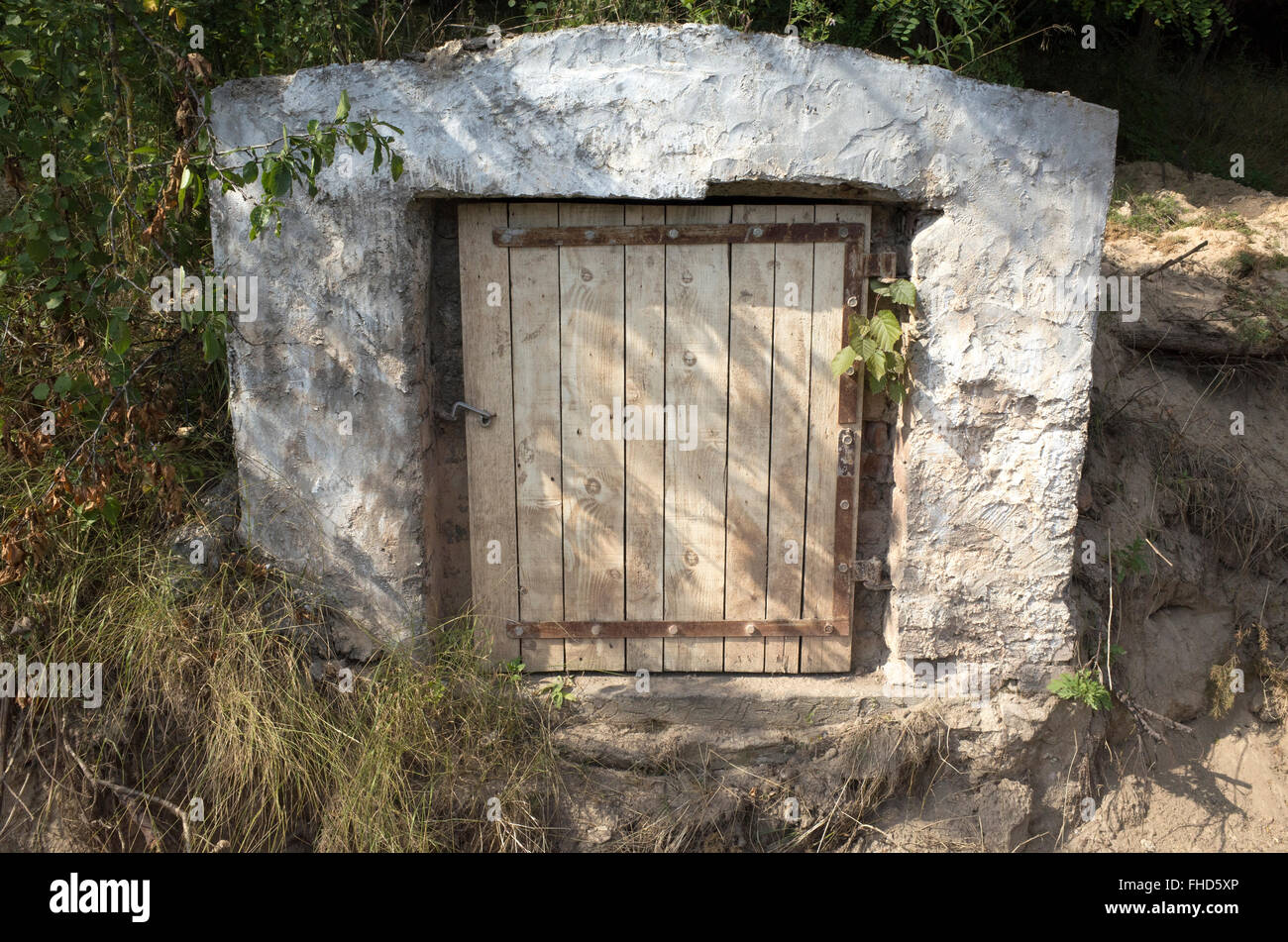 Small mystery door found in side of hill beside road. Rzeczyca Central Poland - Stock Image