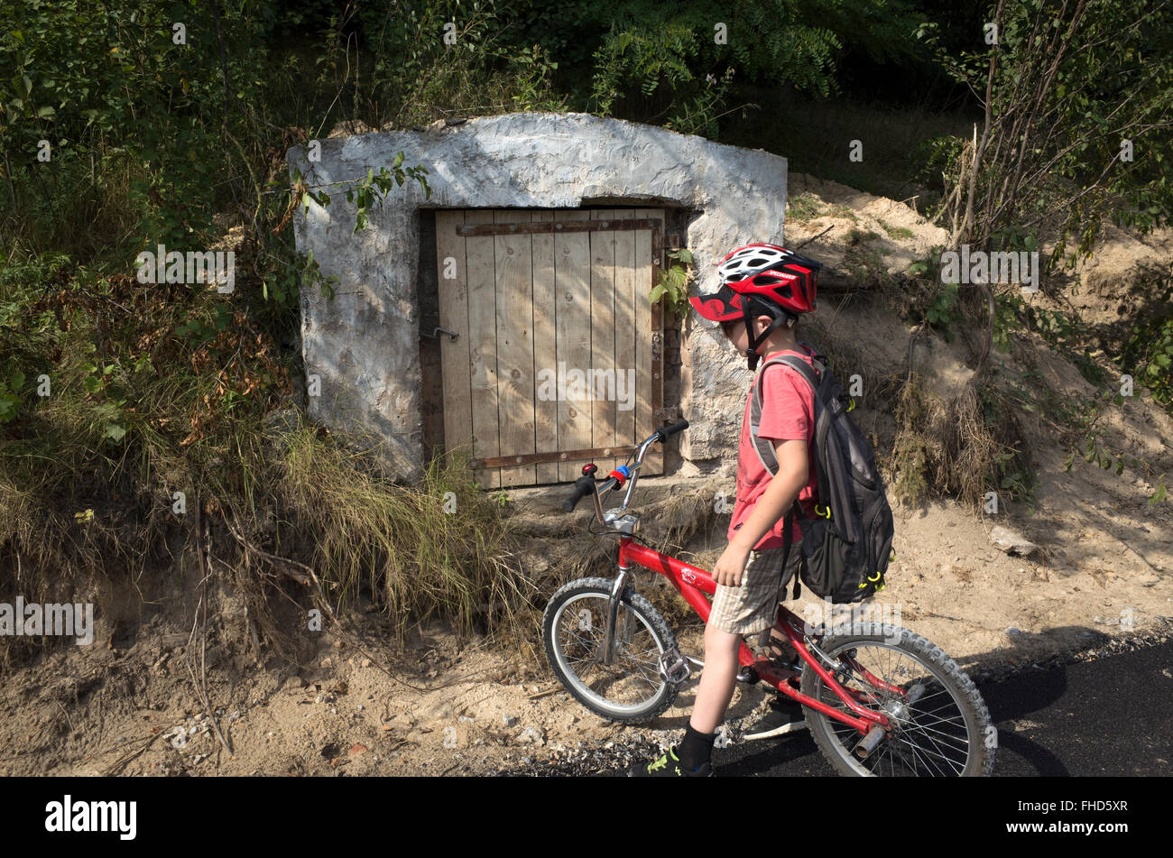 Bicycler contemplates small Hobbit size mystery door in side of hill along the road. Rzeczyca Central Poland - Stock Image