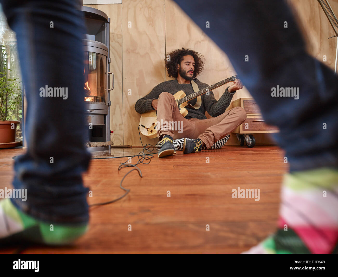 Young man playing electric guitar at the fireplace with person in the foreground - Stock Image