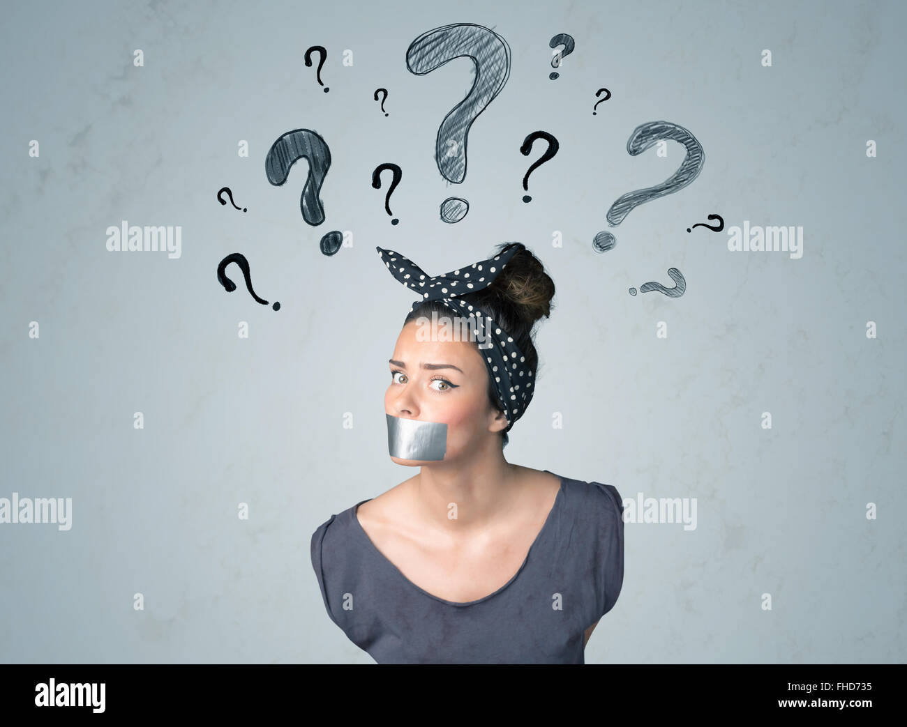 Young woman with glued mouth and question mark symbols - Stock Image