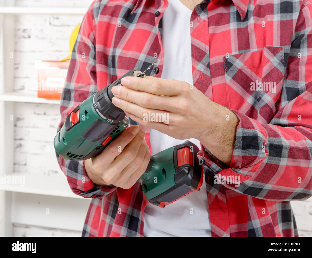 a man using drill. Close-up view of man using drill - Stock Image