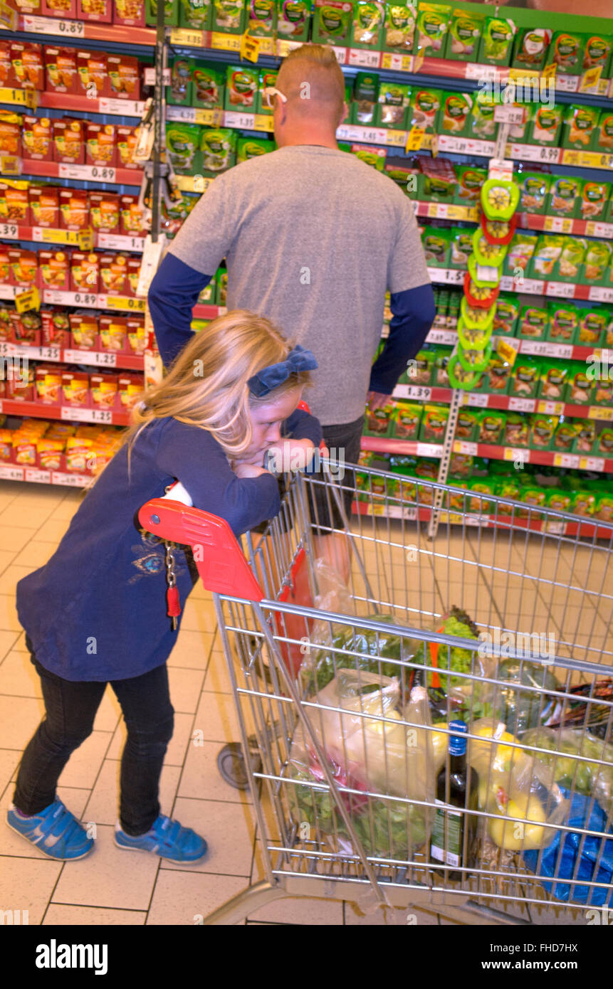 Daughter patiently waits while dad shops in the grocery store. Tomaszow Mazowiecki Central Poland - Stock Image