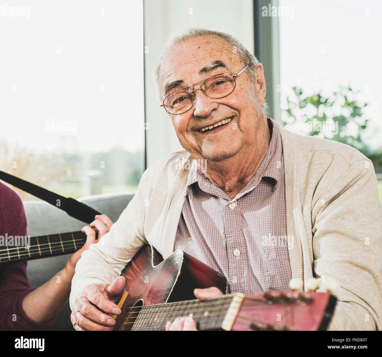 Portrait of senior man playing guitar - Stock Image