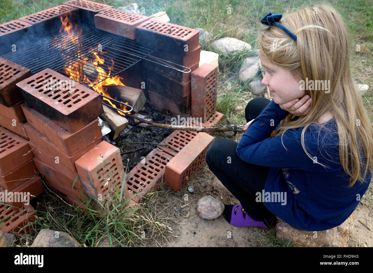 Young Polish girl age 8 musing while poking fire with a stick in outside grill fireplace. Zawady Central Poland - Stock Image