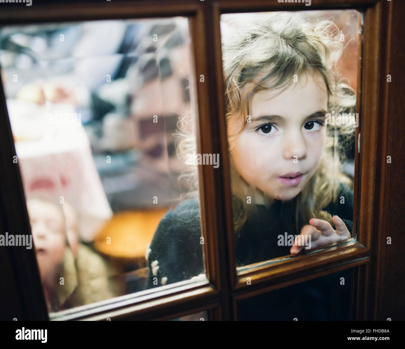 Portrait of little girl looking through a glass pane of a door - Stock Image