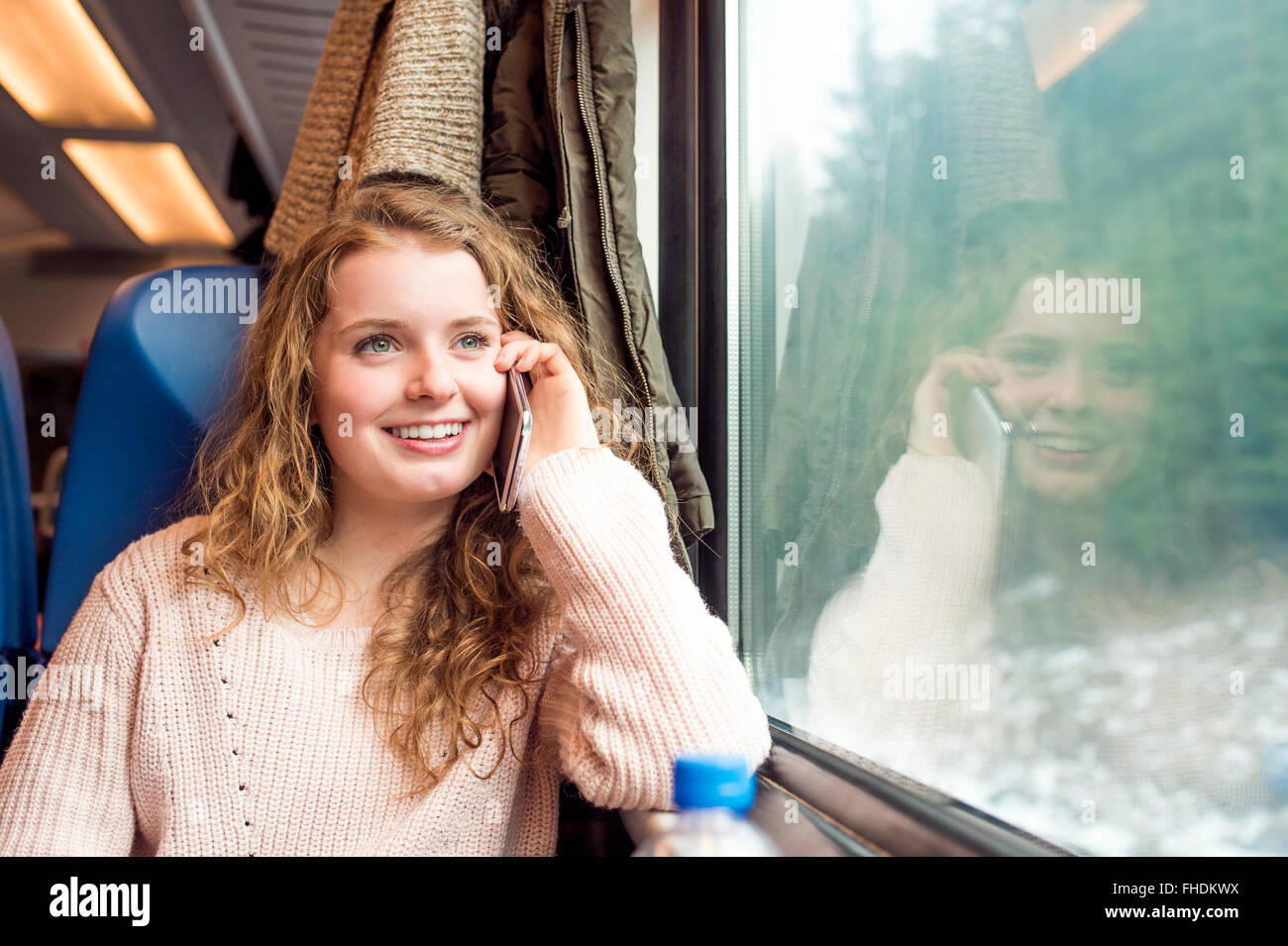 Smiling teenage girl in train car on cell phone - Stock Image
