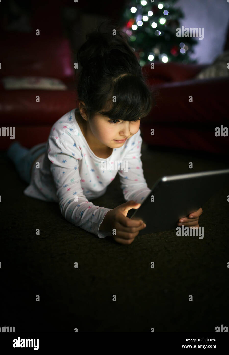 Little girl using digital tablet at home - Stock Image