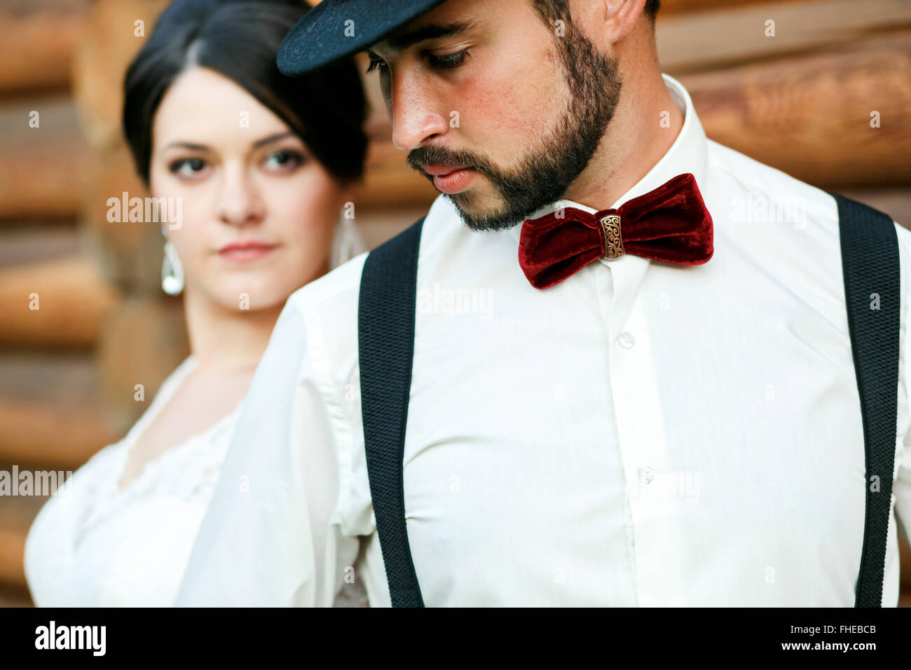Thoughtful groom in hat with beard, mustache, bow tie and suspenders. Bride wearing white wedding dress. Gangster - Stock Image