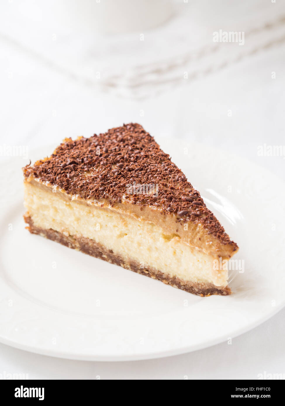 Slice of vegan millet cheesecake with date caramel on a cleat background. - Stock Image
