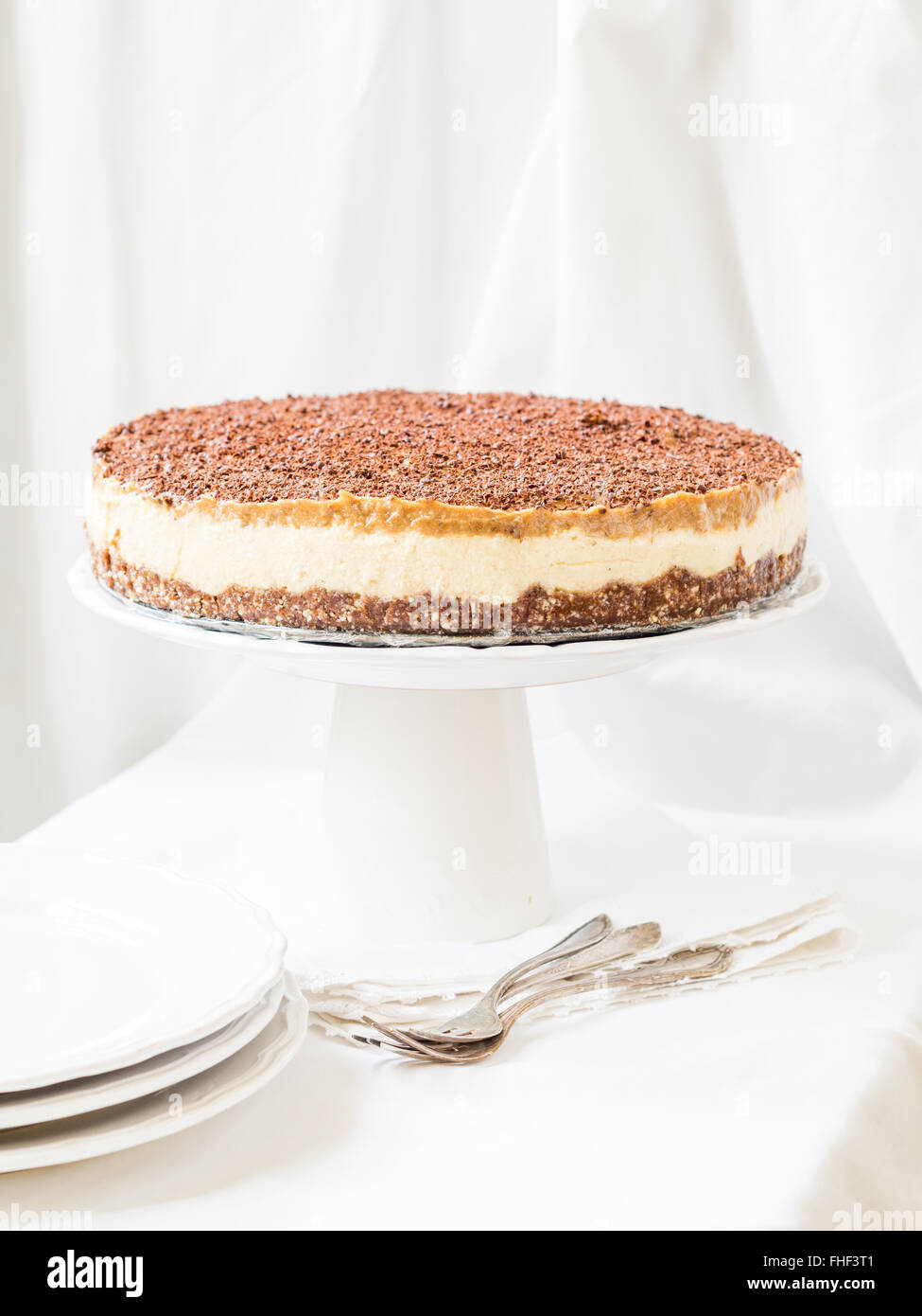 Whole vegan millet cheesecake with date caramel on a cleat background. - Stock Image