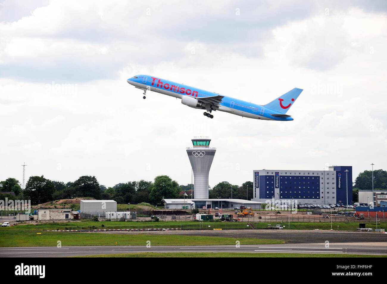 Thomson Airways Boeing 757 200 (G-OOBJ) series taking off over the new control tower at Birmingham Airport, Birmingham, Stock Photo