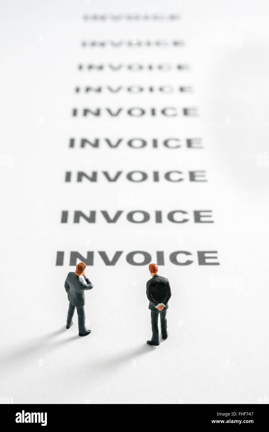 Business men pondering invoices stretching in to the distance a finance or debt concept - Stock Image