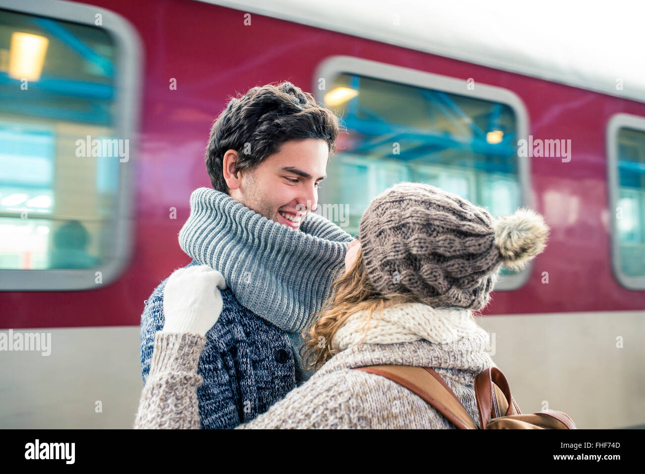 Happy young couple in front of train - Stock Image