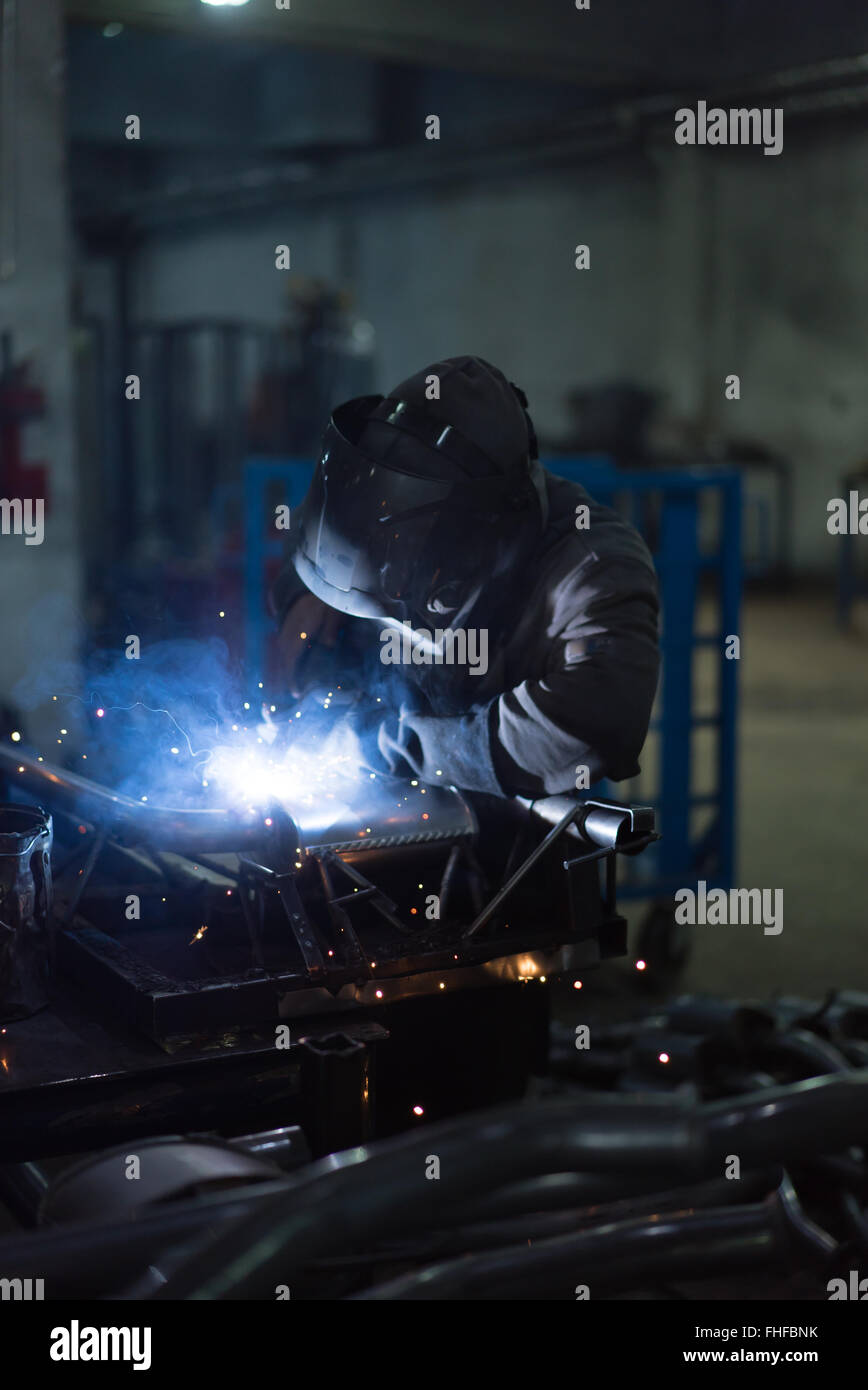 dramatic view of a worker wearing protective gear, welding together pieces of an exhaust pipe, with several other Stock Photo