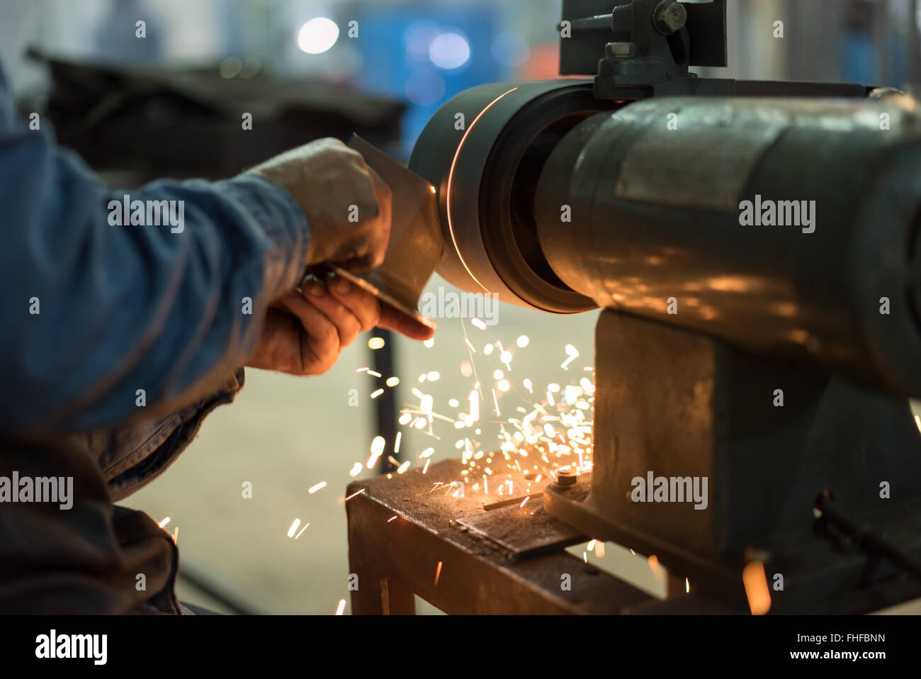 close-up of a worker's hands not wearing gloves, shaping a piece of metal on a bench grinder, with sparks emerging - Stock Image