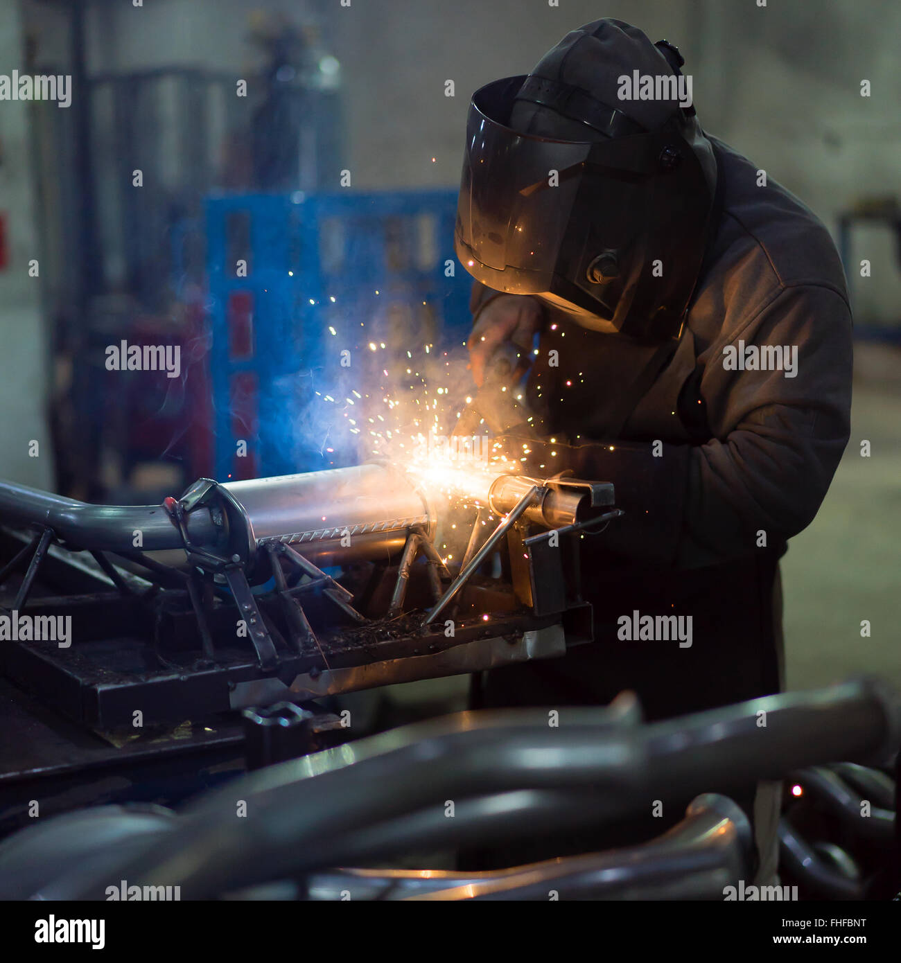 dramatic view of a worker wearing protective gear, welding together pieces of an exhaust pipe, with several other - Stock Image