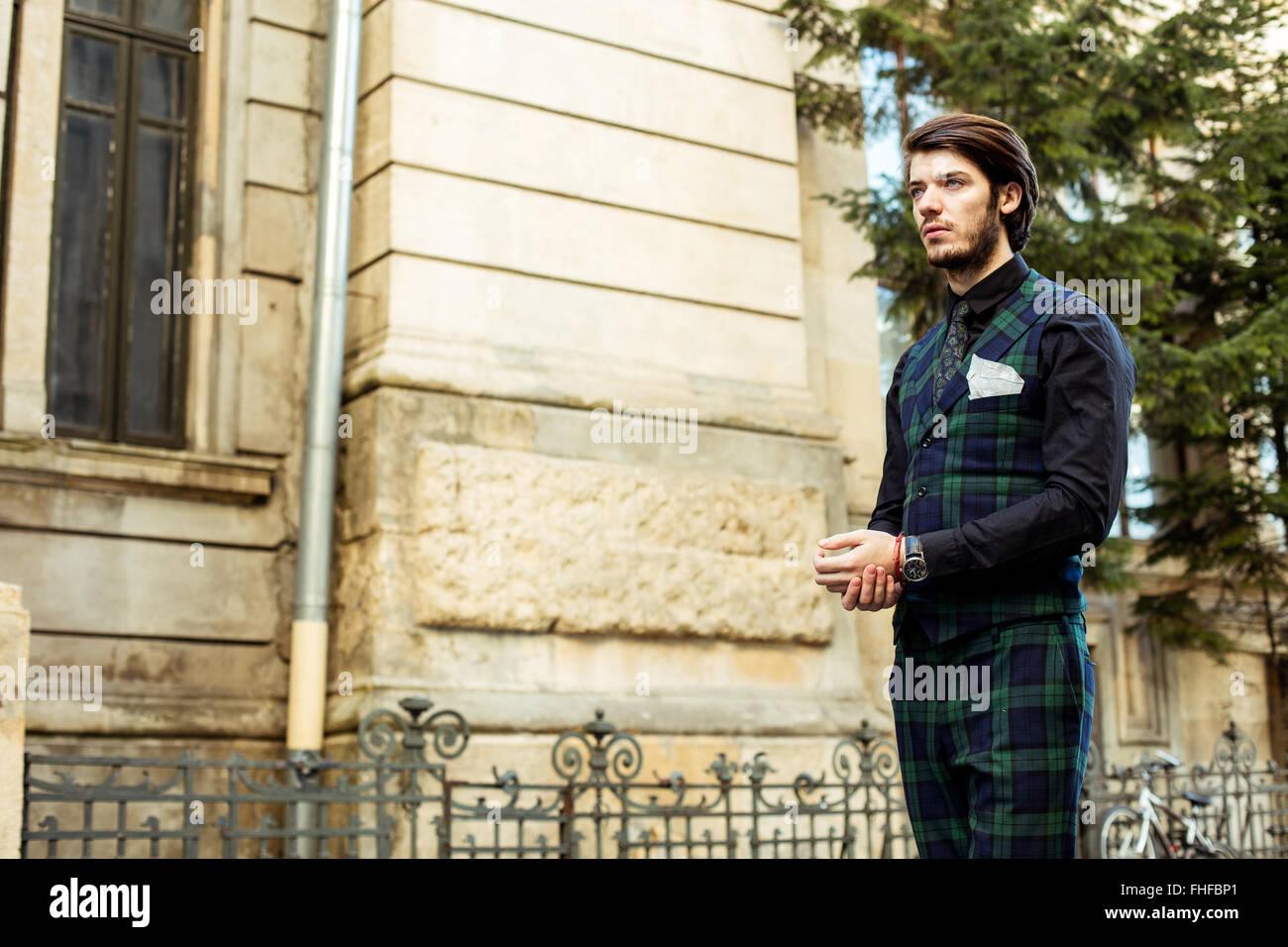 elegant man standing outside, wearing green plaid costume - Stock Image