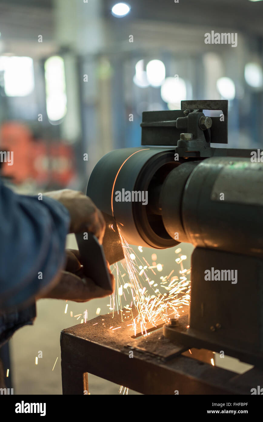 close-up of a worker's hands not wearing gloves, shaping a piece of metal on a bench grinder, with sparks emerging Stock Photo