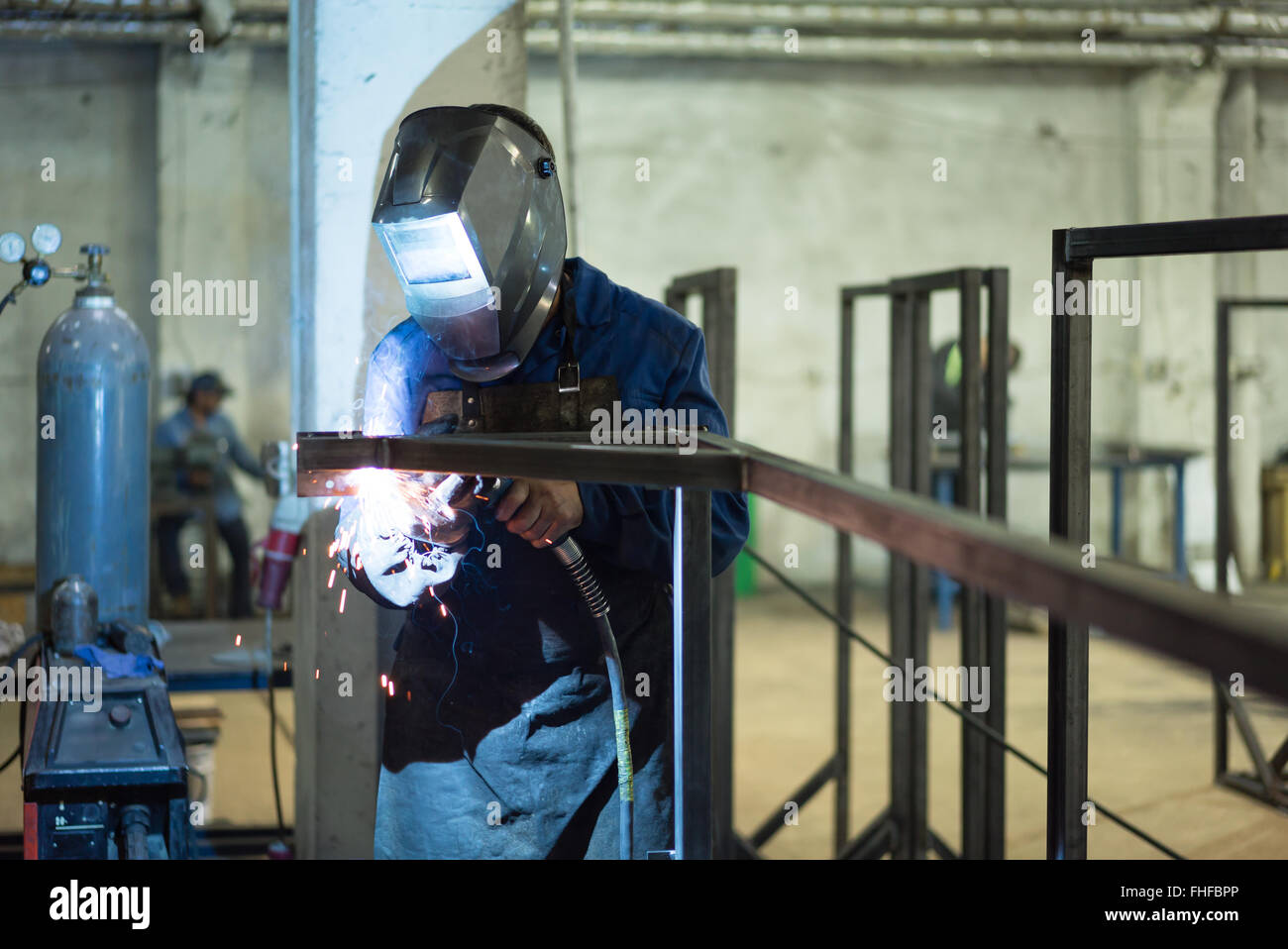 front close-up of a worker wearing protective gear, with mask and a leather apron, welding together two pieces of - Stock Image
