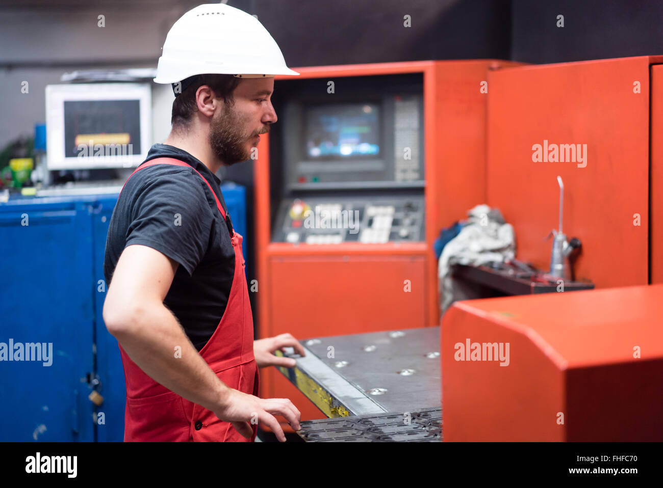 man in red overalls, wearing a white protective helmet, standing, handling a sheet of metal plates onto the table - Stock Image