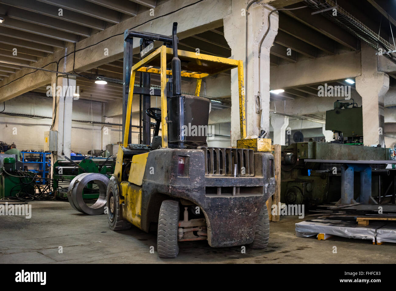 close-up of a yellow forklift, with no driver, parked inside an industrial hall, with green industrial machinery Stock Photo