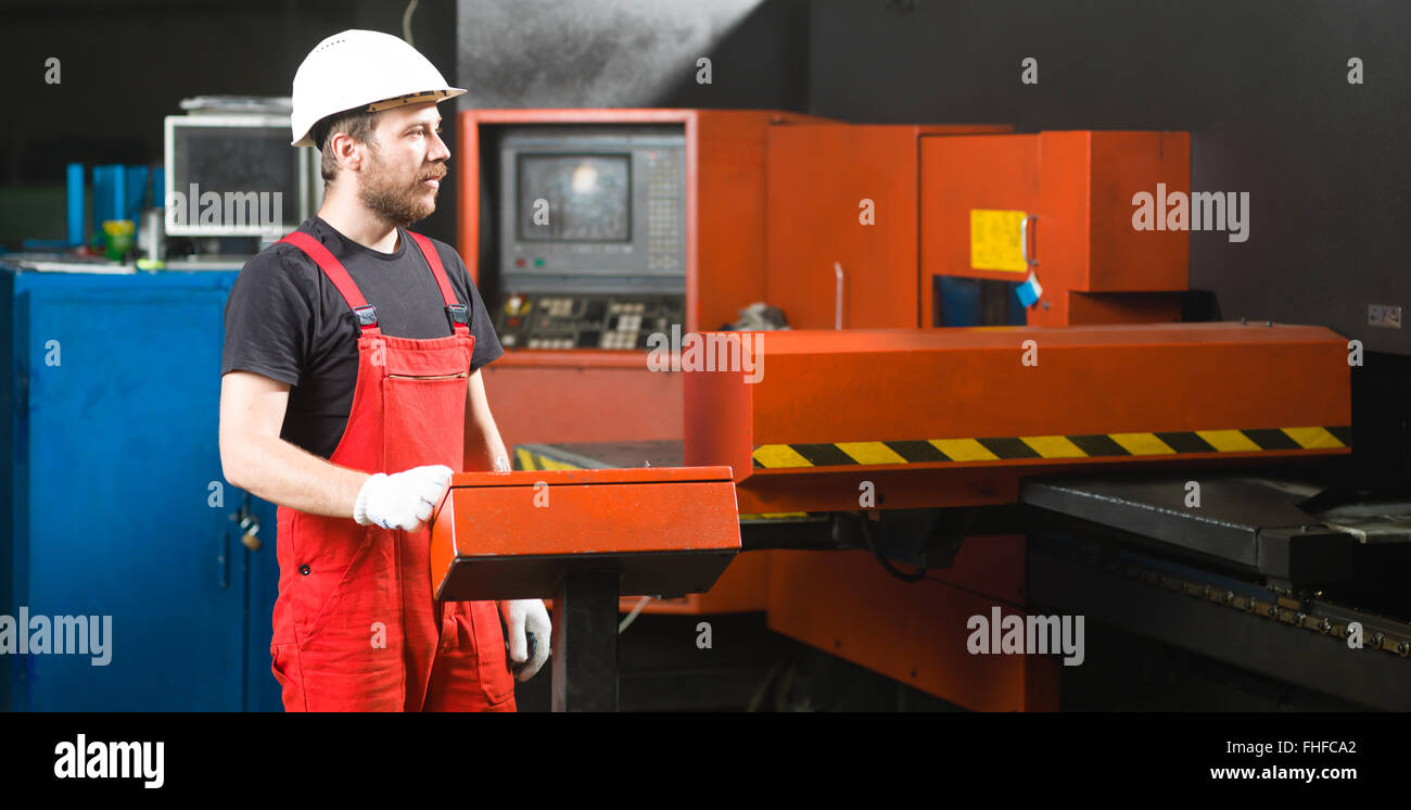front view of a worker looking in the distance, wearing red overalls, white protective helmet and gloves, standing - Stock Image