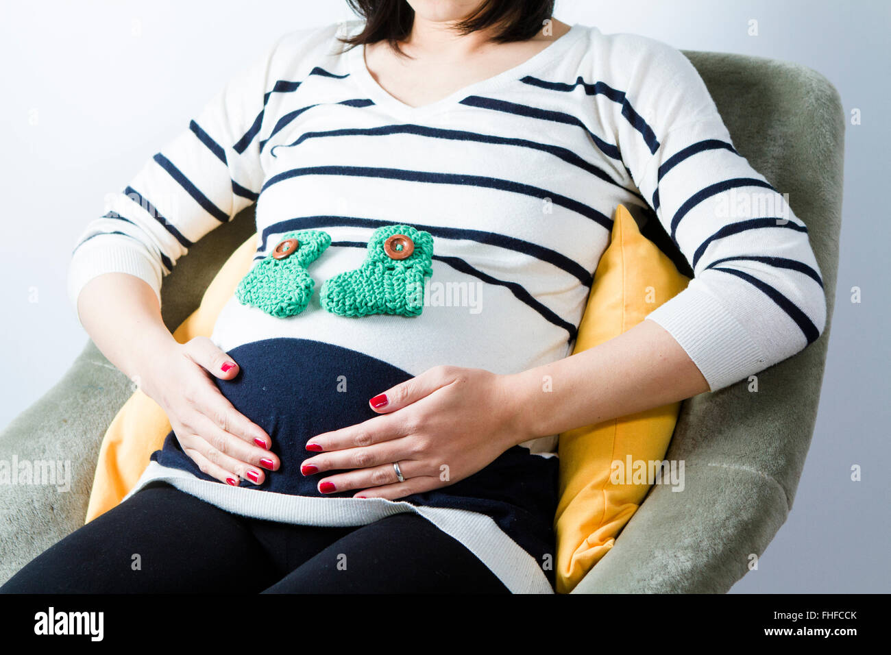 Pregnant woman sitting with baby's socks on belly - Stock Image