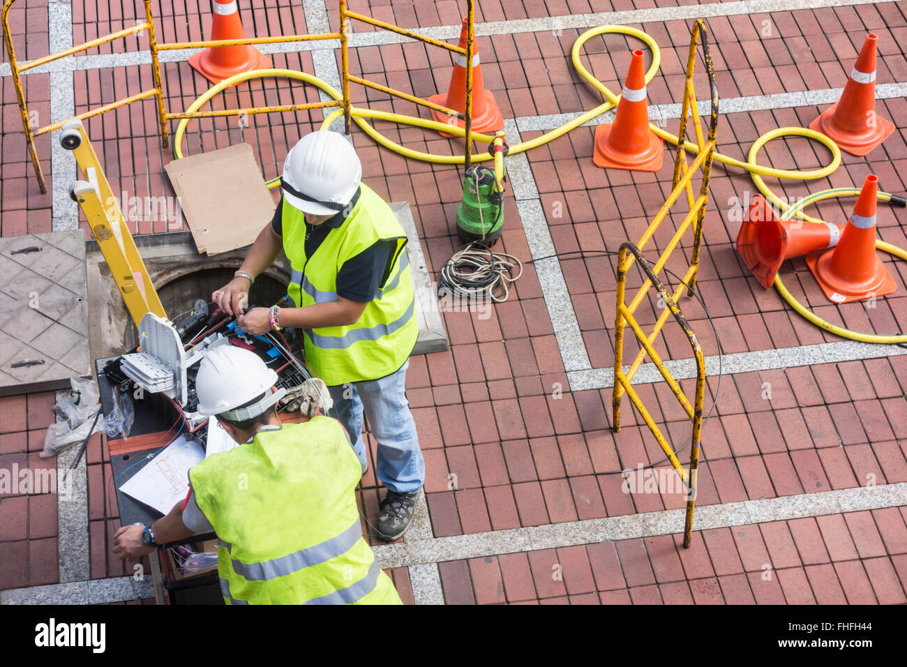 Telephone engineers (male and female) installing fibre optic cables. - Stock Image