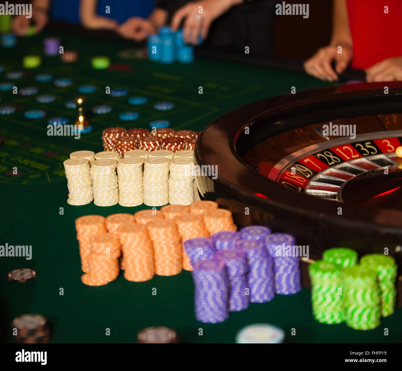 green roulette table with collored chips ready to play - Stock Image