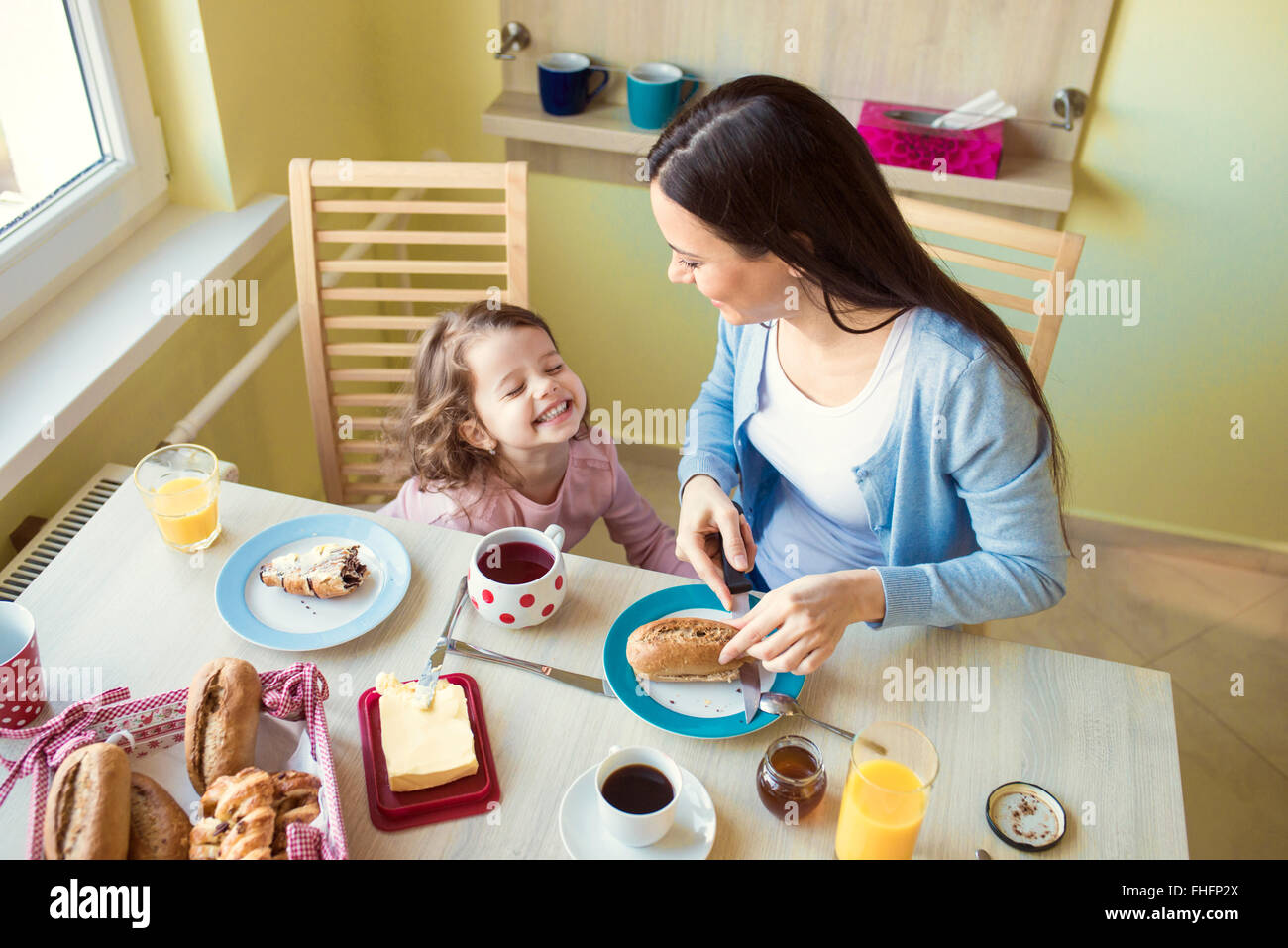 Mother and her little daughter at breakfast table - Stock Image