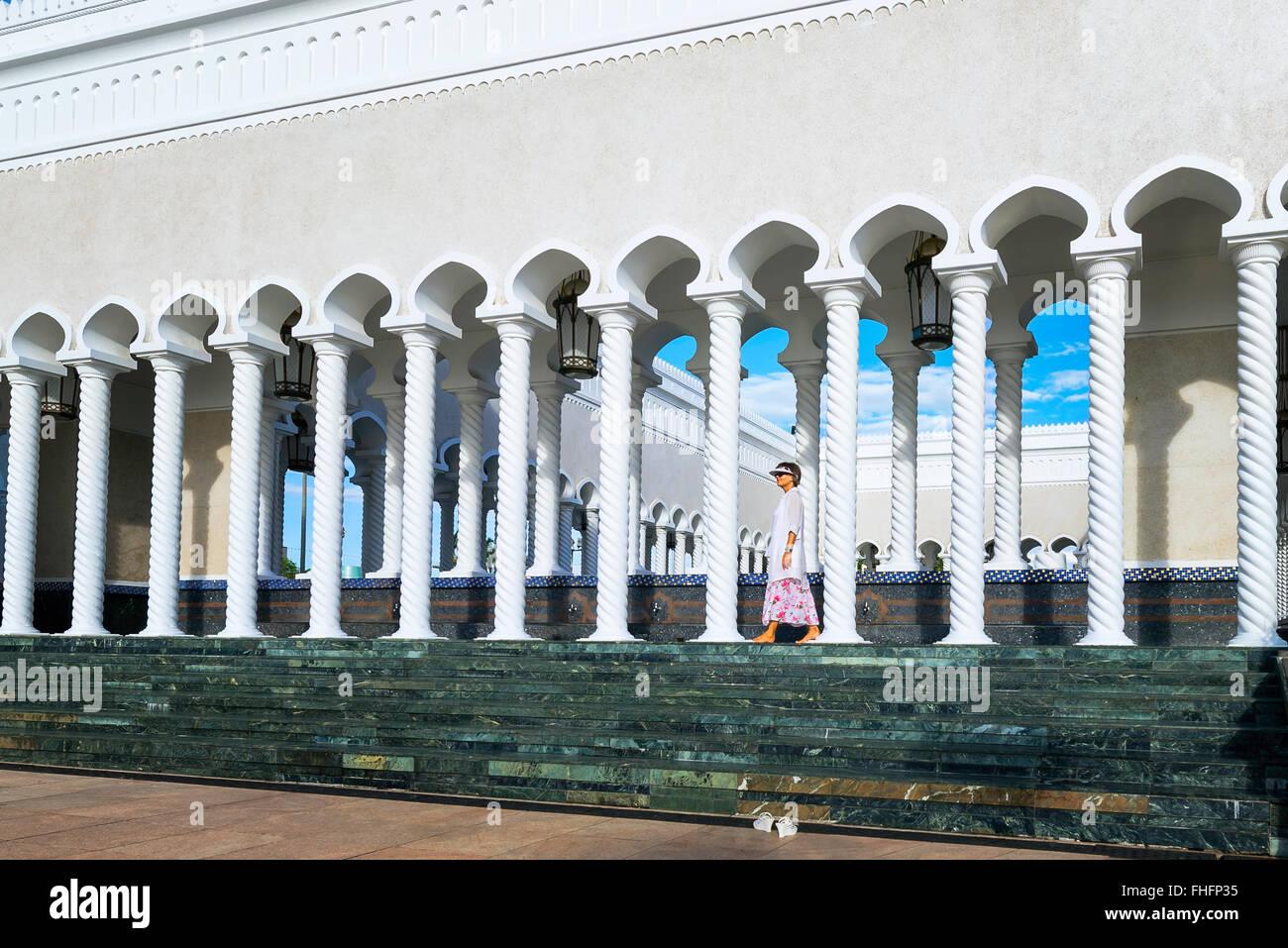 Woman walking on Sultan Omar Ali Saifuddin Mosque in Brunei - Stock Image