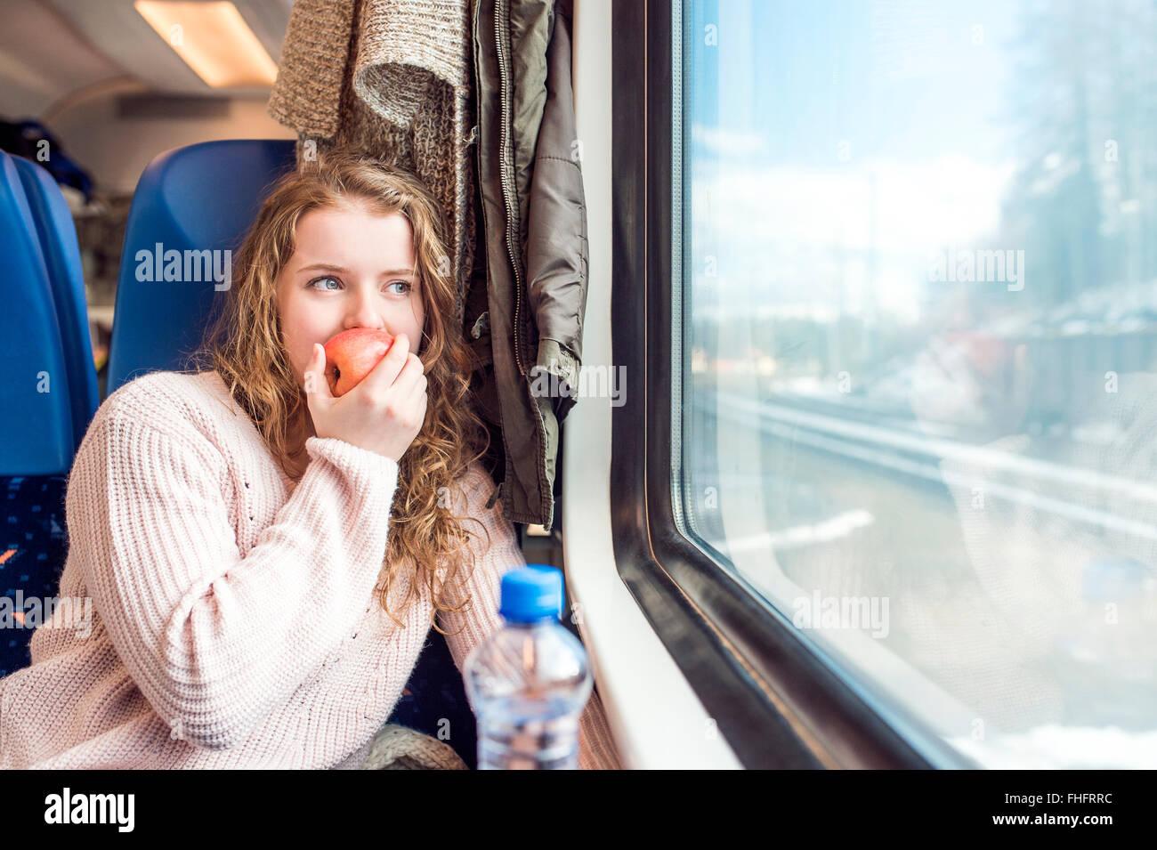 Teenage girl in train car eating an apple - Stock Image