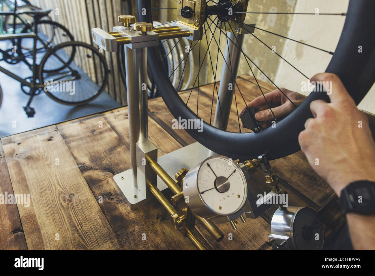 Mechanic working on tire in a custom-made bicycle store - Stock Image