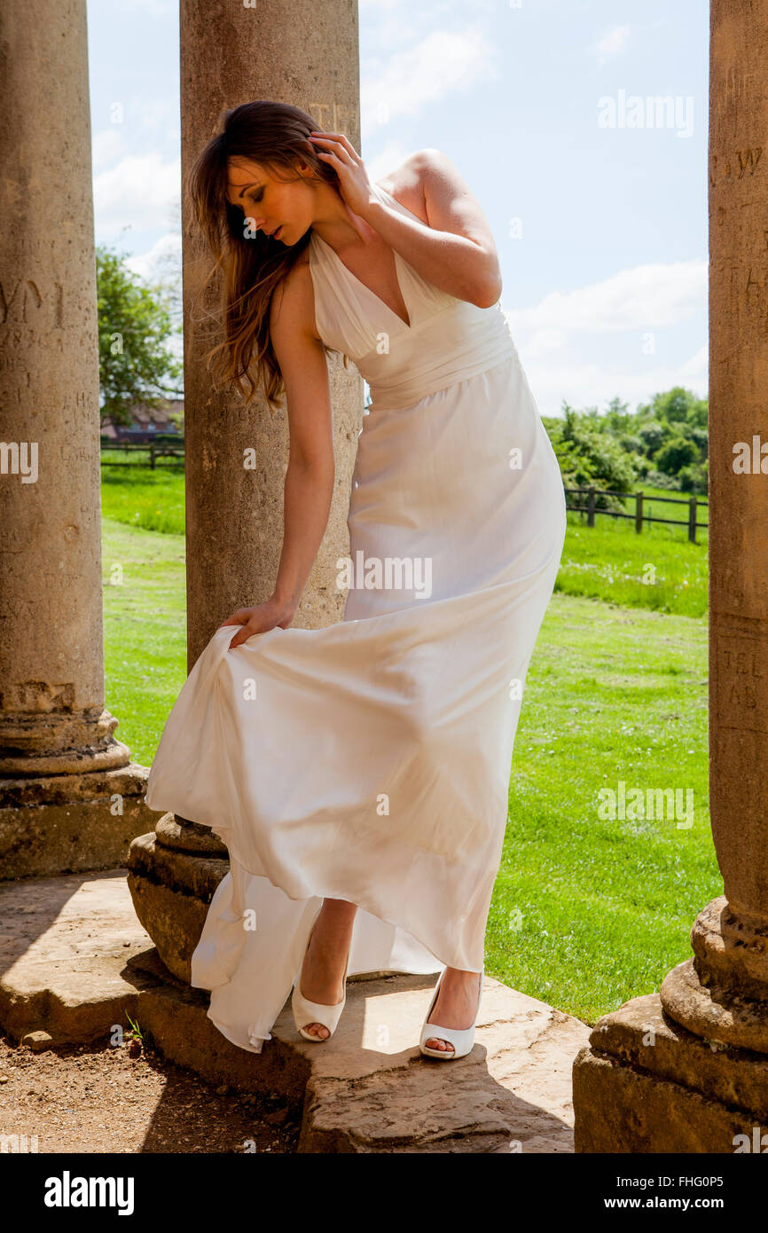 Lady in white ballgown on portico of ruined building Stock Photo