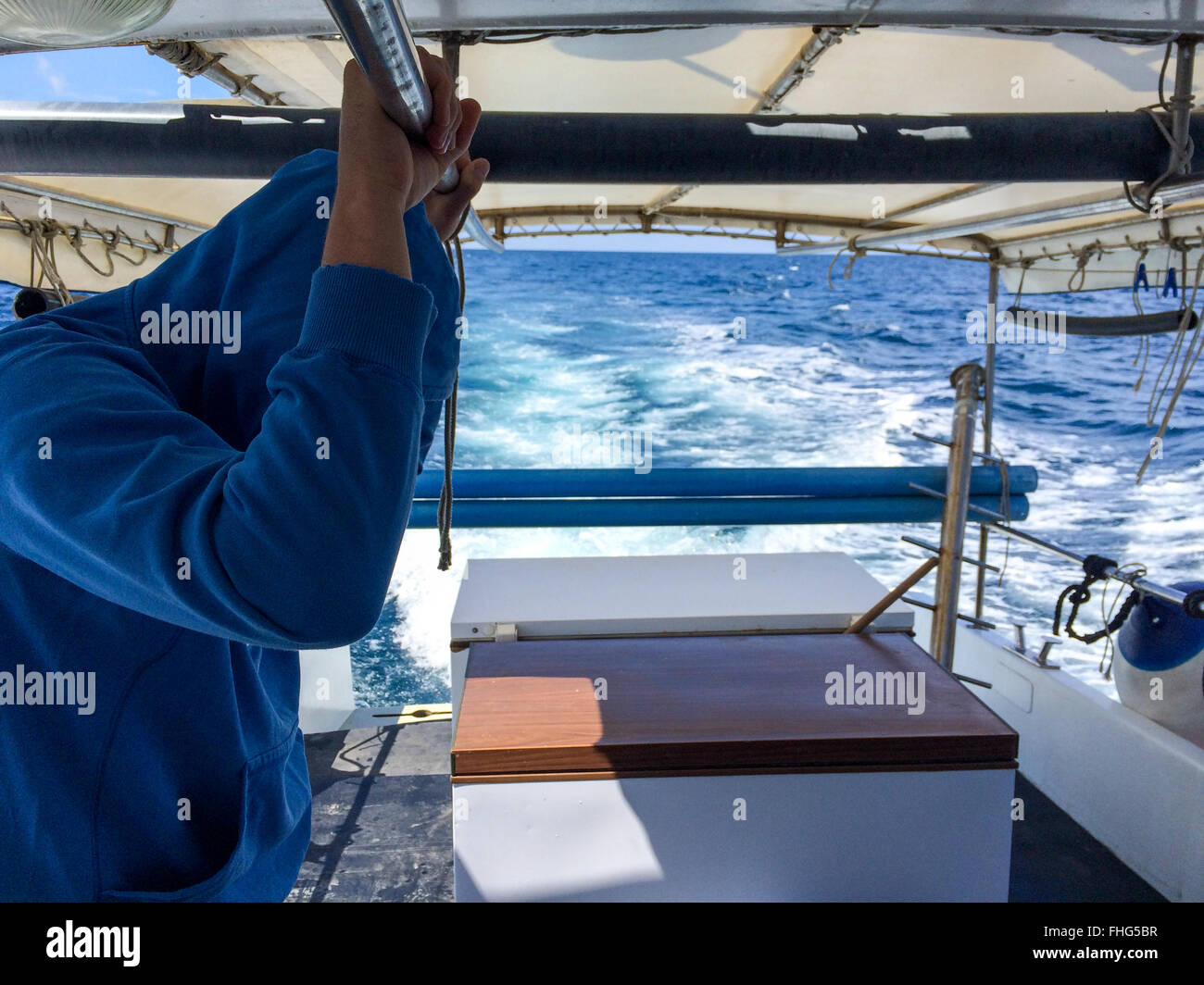 Worker on fishing boat waiting during navigation - Stock Image