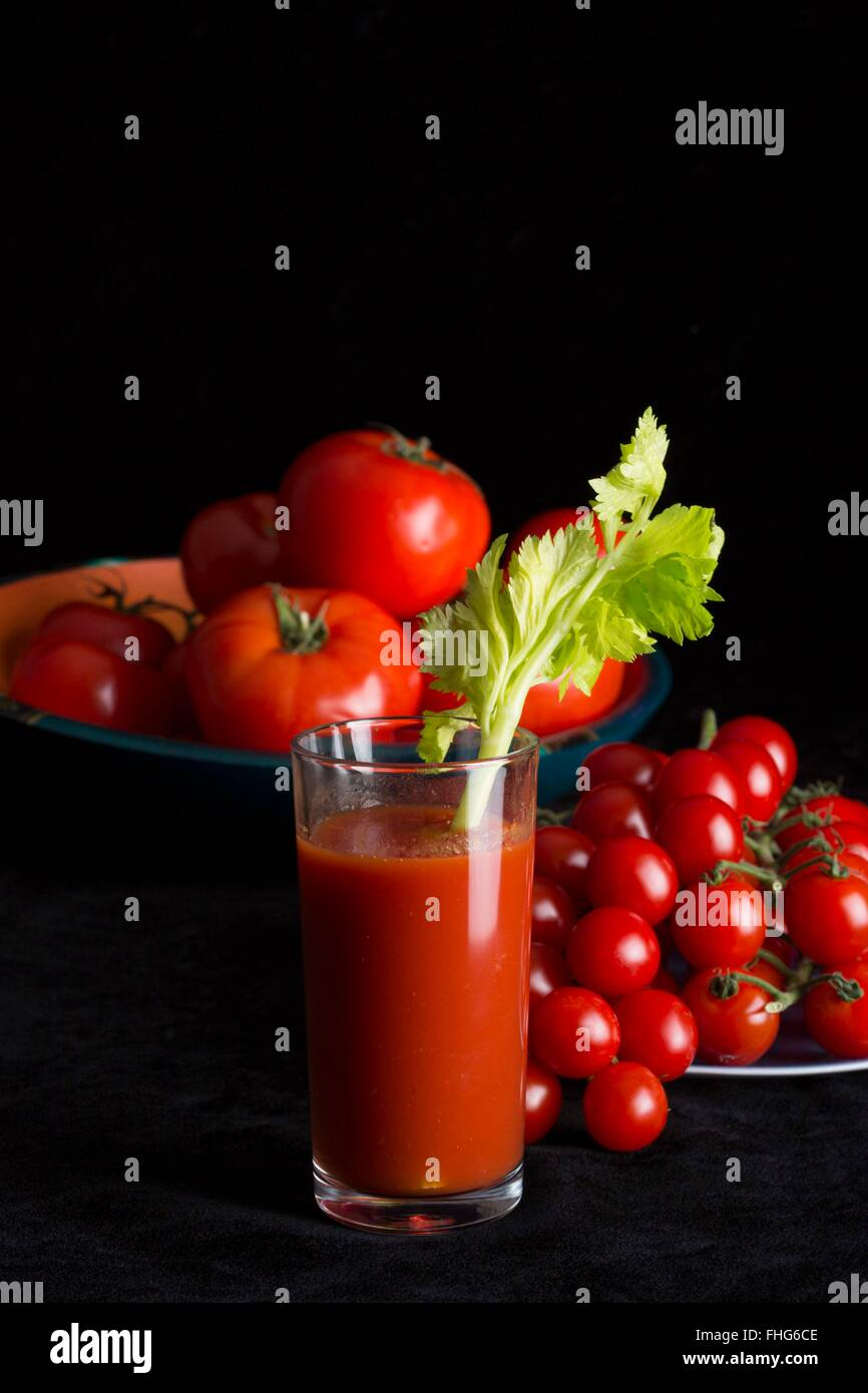 Hero shot of a glass of tomato juice with a stalk of celery and raw tomatoes on a dramatic black backdrop with copy - Stock Image
