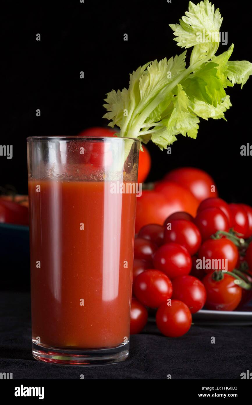 Hero shot of a tall glass of tomato juice with a stalk of celery with fresh tomatoes and a black background - Stock Image