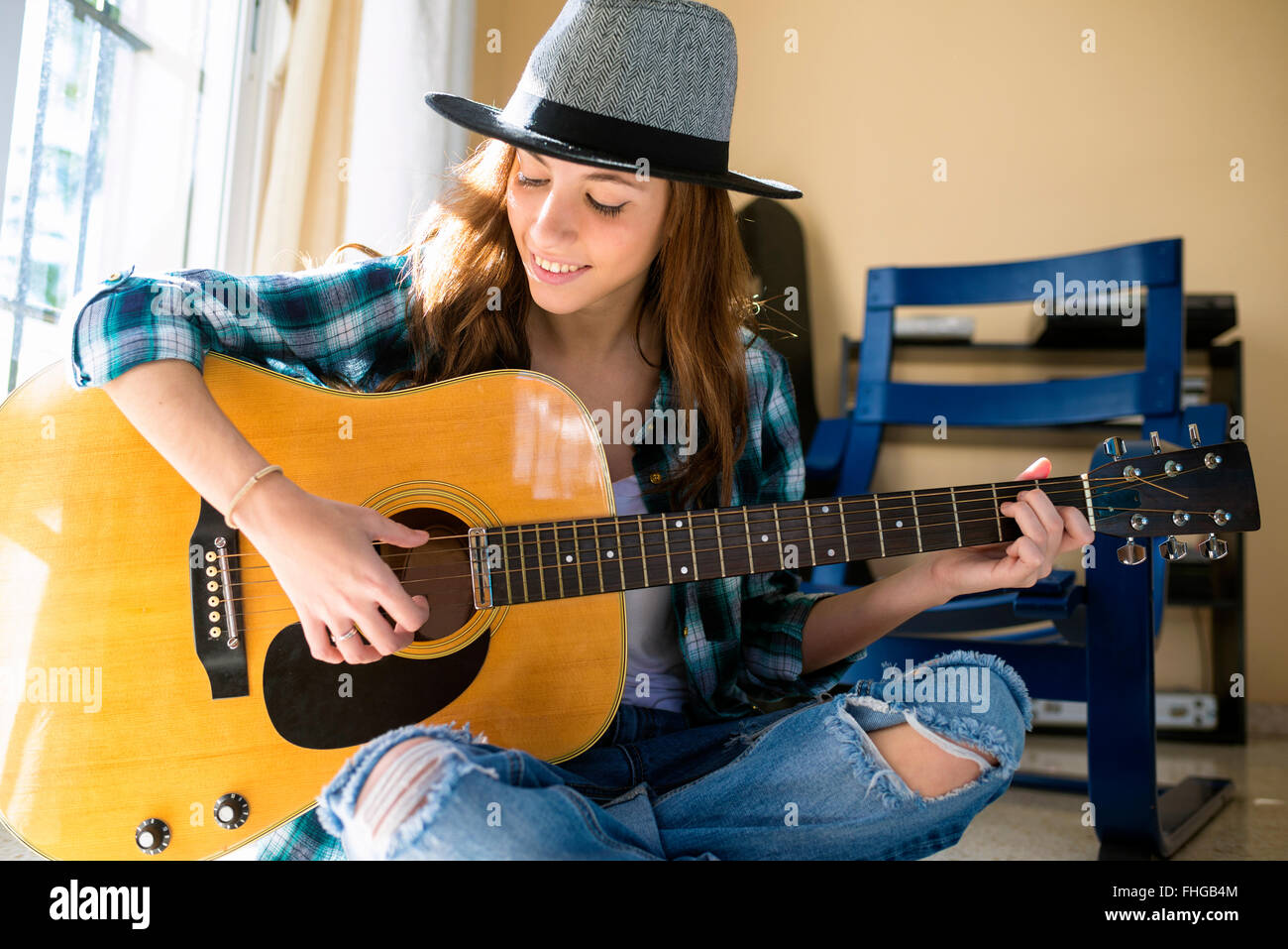 Smiling young woman playing guitar indoors - Stock Image