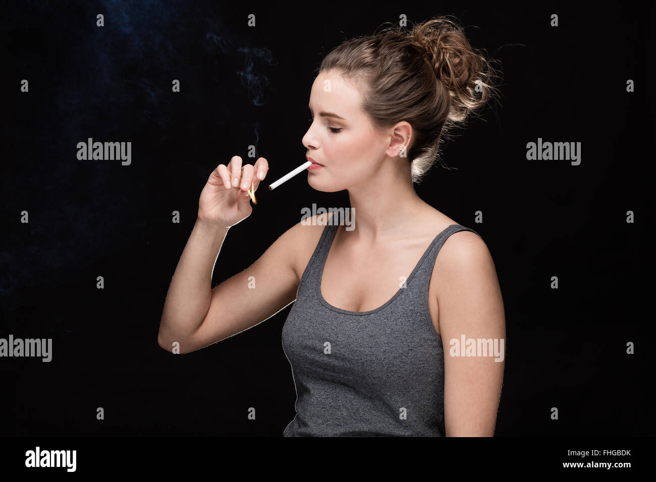 young woman with cigarette, smoking concept on black background - Stock Image
