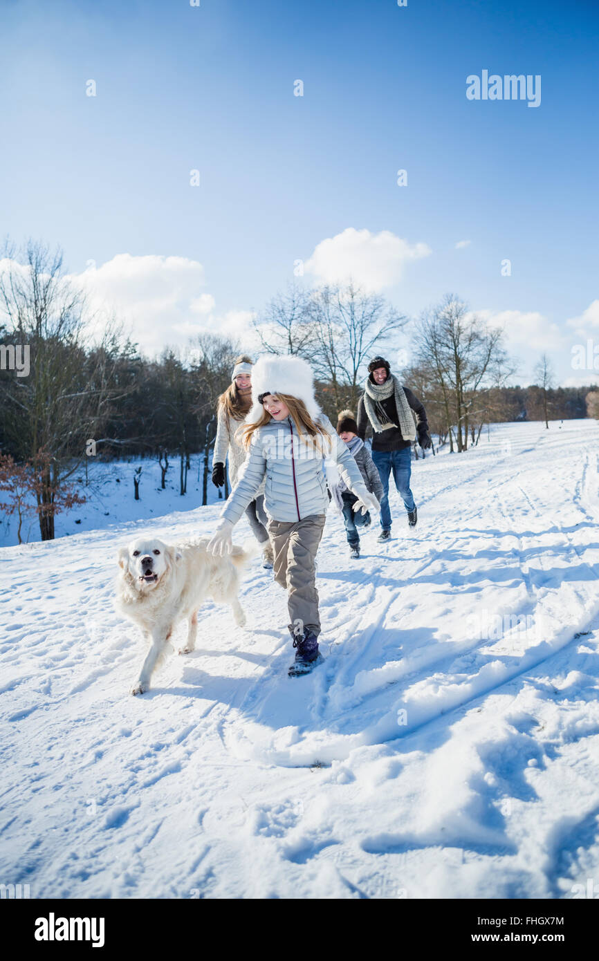 Family walking together in the snow - Stock Image