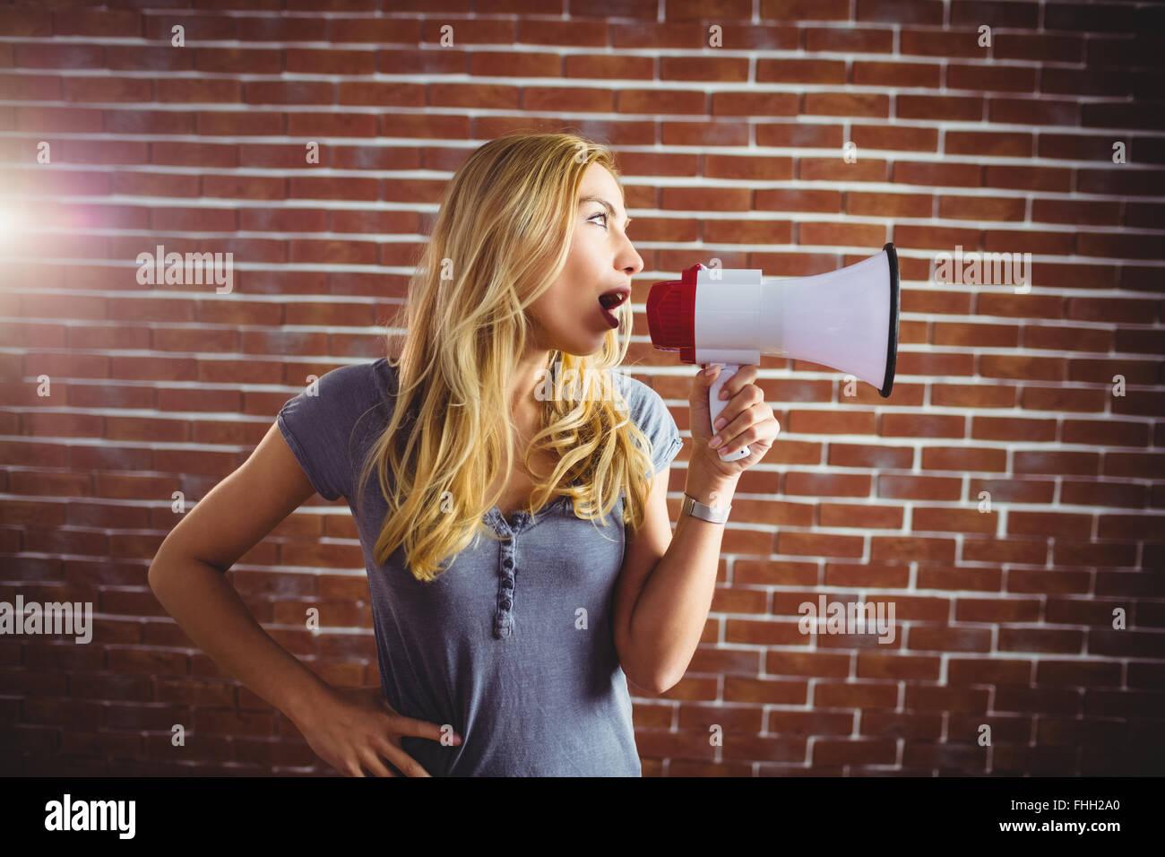 Woman yelling through megaphone - Stock Image
