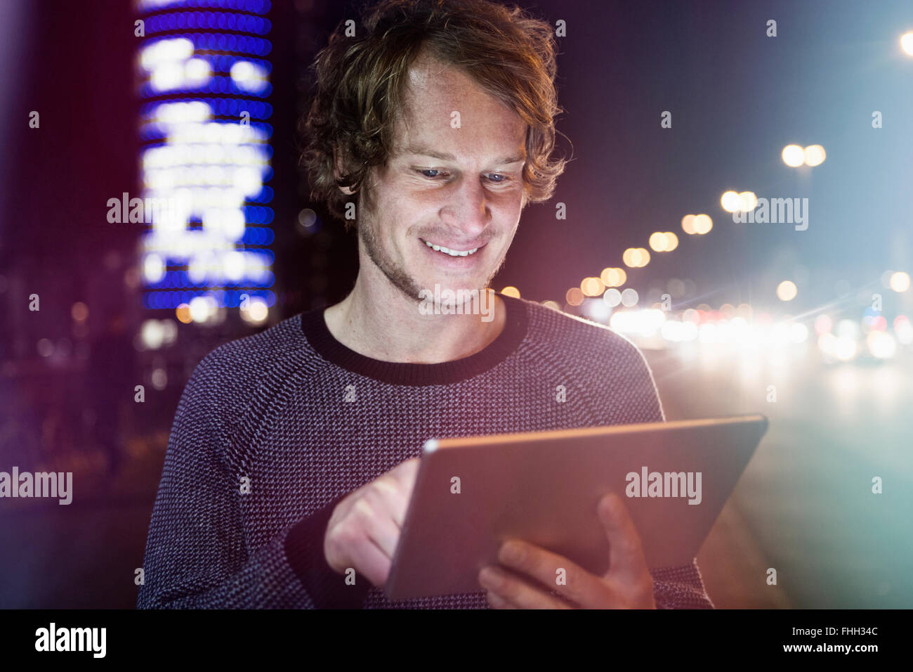 Germany, Munich, portrait of smiling man using digital tablet at night - Stock Image