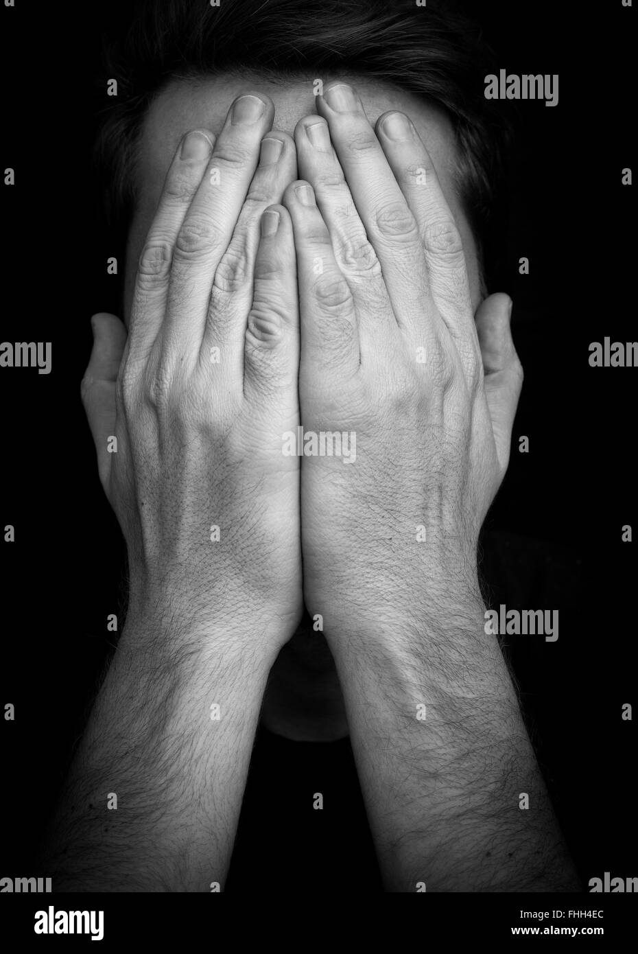 Depression concept – man covering face with hands - Stock Image