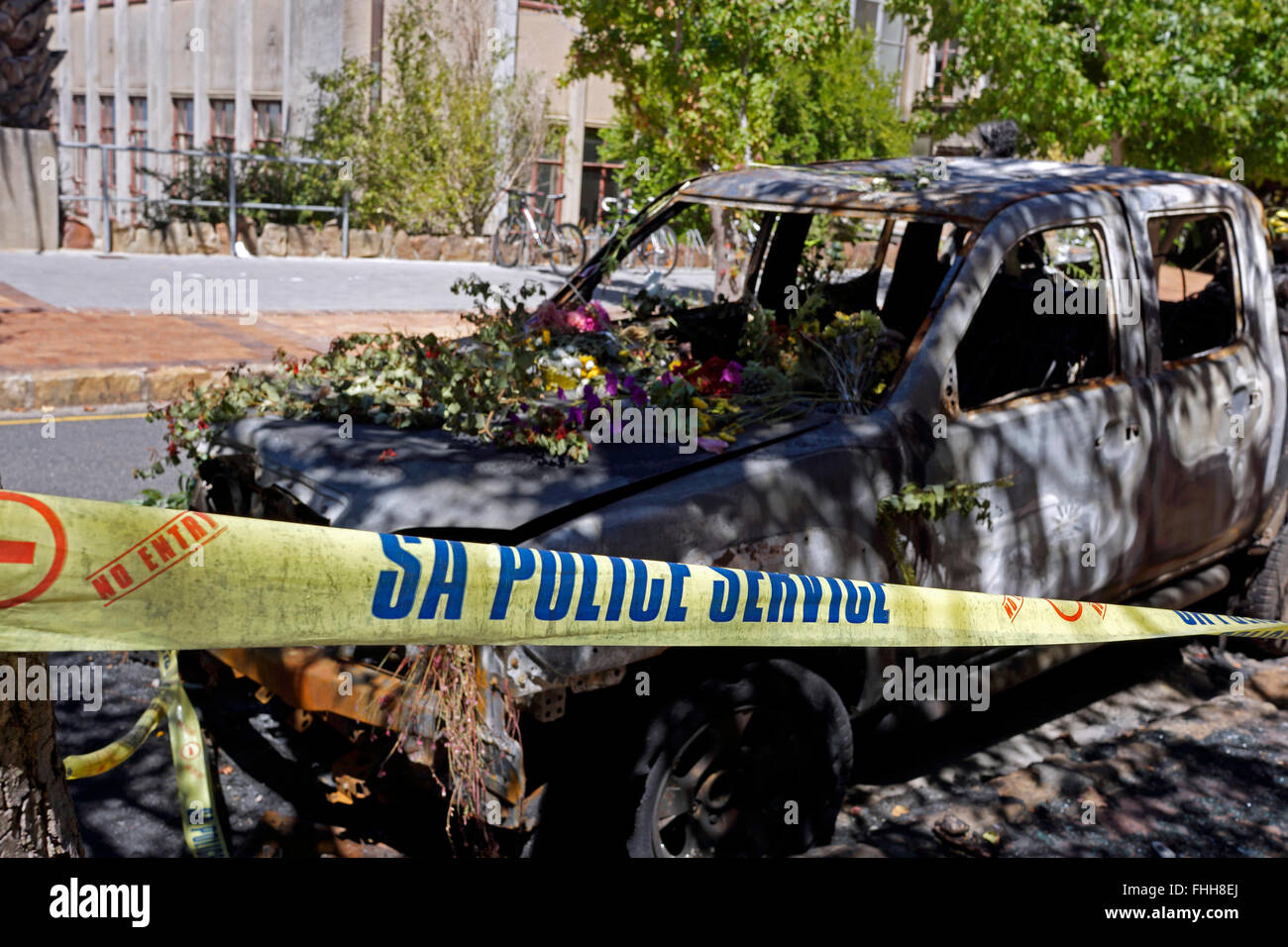 Cape Town, South Africa. 25th  February 2016. A burnt out UCT vehicle is adorned with fresh flowers. The vehicle - Stock Image