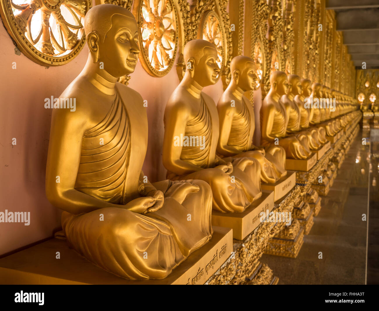 Alignment of Buddhas statues in temple, Thailand - Stock Image