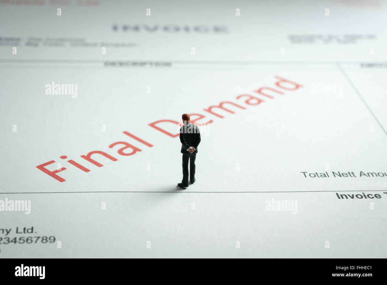 Miniature business man gloomily pondering an overdue final demand invoice a finance or debt concept - Stock Image